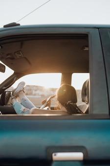 Młoda podróżnik kobieta bawić się gitarę w samochodzie jeepa 4x4 robi podróżowi wakacje o zachodzie słońca w lecie