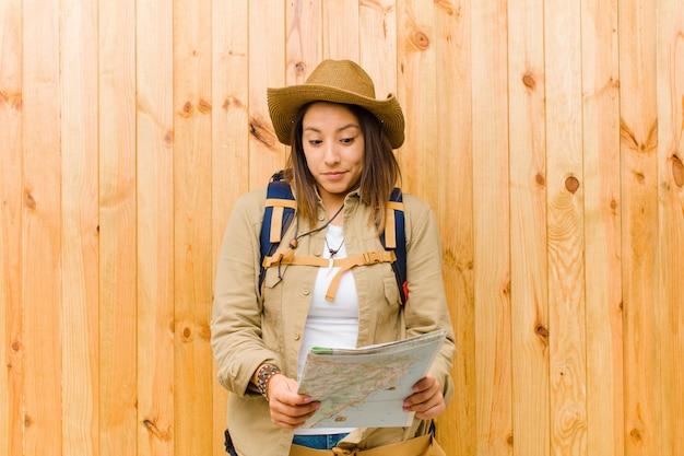 Młoda podróżnik kobieta z mapą przeciw drewno ścianie