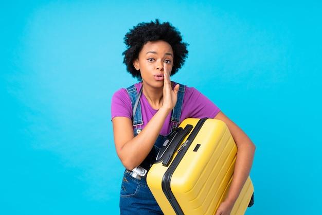 Młoda podróżnik kobieta z walizką nad odosobnioną ścianą