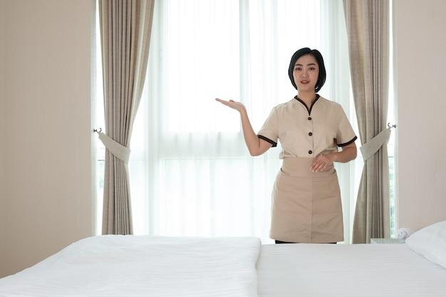 Młoda pokojówka asia w pokoju hotelowym, jej toaleta przed kamerą