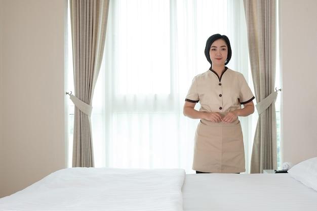 Młoda pokojówka asia w pokoju hotelowym patrzy w kamerę