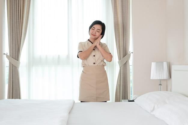 Młoda pokojówka asia w pokoju hotelowym