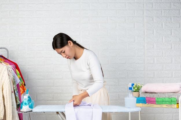 Młoda pokojówka przygotowująca koszulę na desce do prasowania z białej cegły.