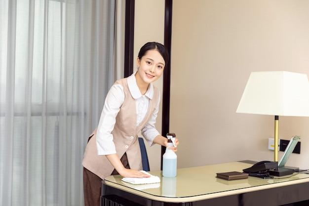 Młoda pokojówka sprzątająca pokoje hotelowe