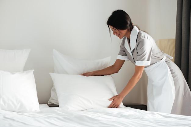 Młoda pokojówka ustawia poduszkę na łóżku