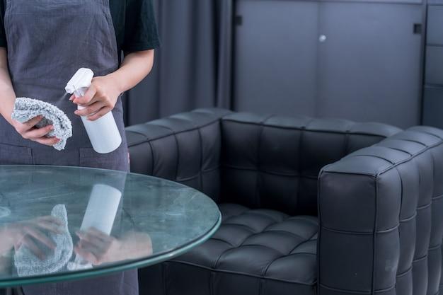 Młoda pokojówka w fartuchu czyści, wyciera powierzchnię biurowego szklanego stołu środkiem do czyszczenia butelek z rozpylaczem, mokrą szmatką, zbliżenie, styl życia, prawdziwi ludzie.