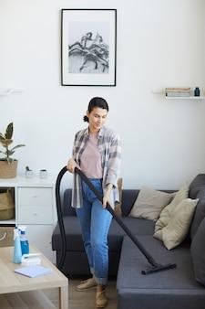 Młoda pokojówka za pomocą odkurzacza w salonie odkurza kurz z sofy