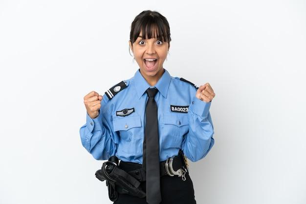 Młoda policja mieszana rasa kobieta na białym tle świętuje zwycięstwo w pozycji zwycięzcy