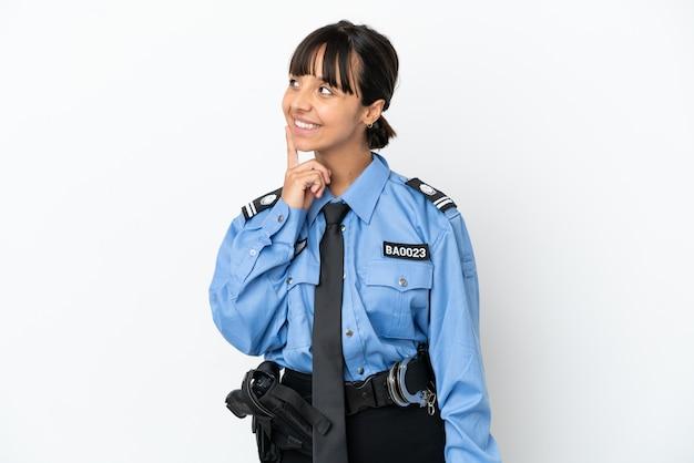Młoda policja mieszanej rasy kobieta na białym tle myśląca o pomyśle, patrząc w górę