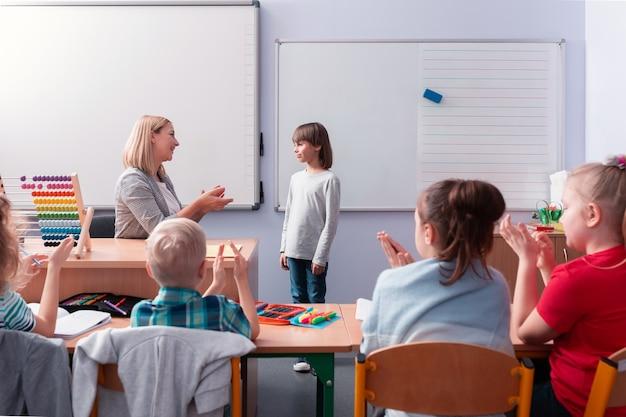 Młoda pomocna nauczycielka rozmawia z uczniem stojącym przy tablicy