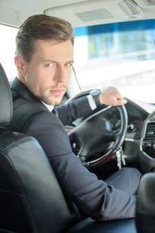 Młoda pomyślna biznesmen jazda w samochodzie.