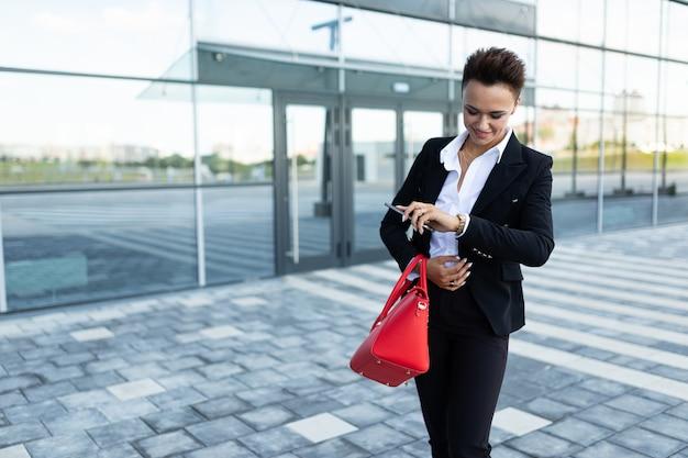 Młoda pomyślna biznesowa dama z czerwoną torebką