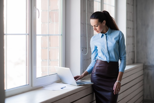 Młoda pomyślna szczęśliwa uśmiechnięta biznesowa kobieta na laptopie