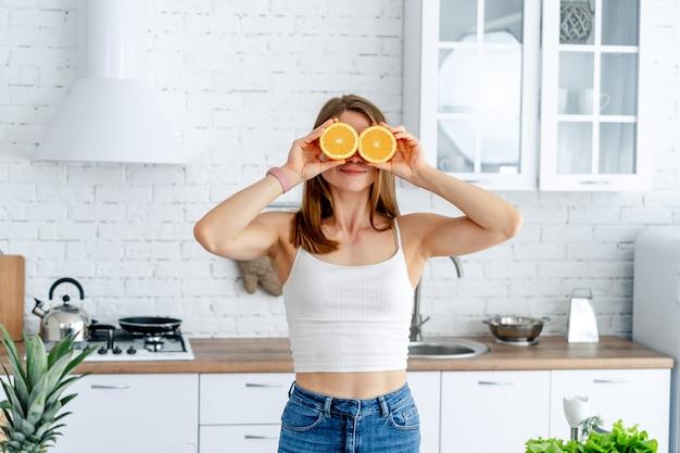 Młoda powabna kobieta trzyma dwie połówki pomarańcze blisko jej pięknej twarzy w kuchni. koncepcja zdrowej żywności.
