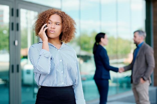 Młoda poważna bizneswoman rozmawia z jednym z partnerów przez telefon, podczas gdy jej koledzy uścisk dłoni na tle
