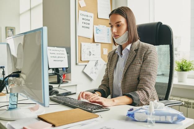 Młoda poważna bizneswoman z maską ochronną włókienniczych na brodzie naciskając przyciski na klawiaturze komputera podczas pracy w biurze