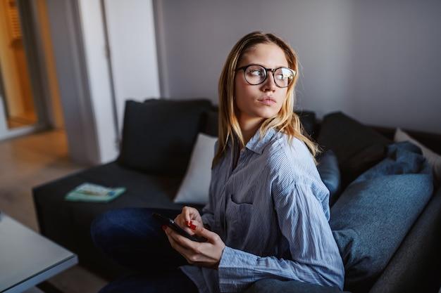 Młoda poważna caucasian blond kobieta siedzi na kanapie w żywym pokoju z eyeglasses, trzyma mądrze telefon i przyglądającego koryta okno.