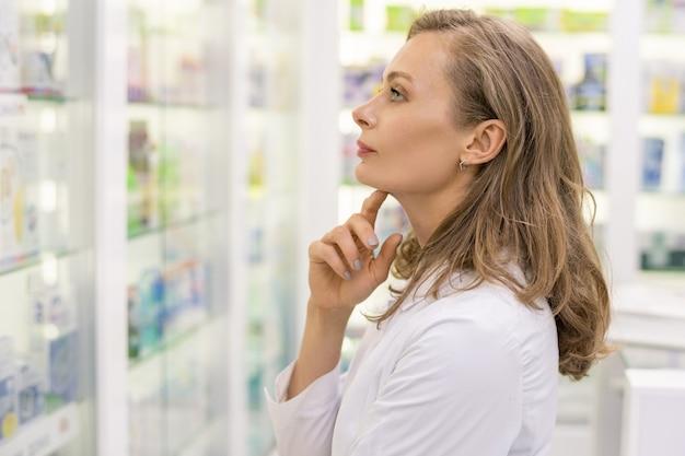 Młoda, poważna farmaceutka lub konsultantka współczesnej drogerii, patrząc na asortyment nowego leku, stojąc przy dużym wyświetlaczu