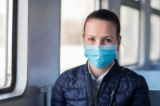 Młoda poważna kobieta jest ubranym medyczną ochronną maskę na jej twarzy przeciw coronavirusowi, piękna dziewczyna siedzi samotnie w pociągu, transport publiczny. wirus koronowy, pandemia, covid-19, zdrowie, koncepcja podróży