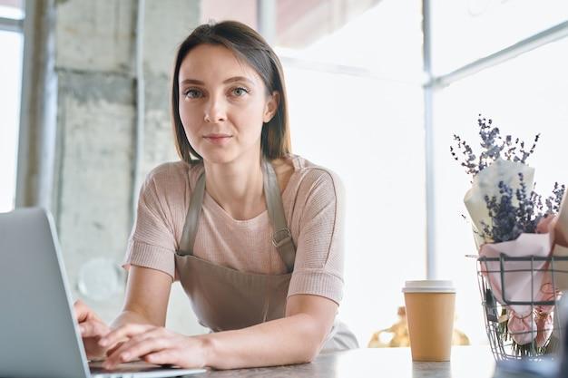 Młoda poważna kobieta w odzieży roboczej, patrząc na ciebie podczas przeglądania sieci przed laptopem w studio