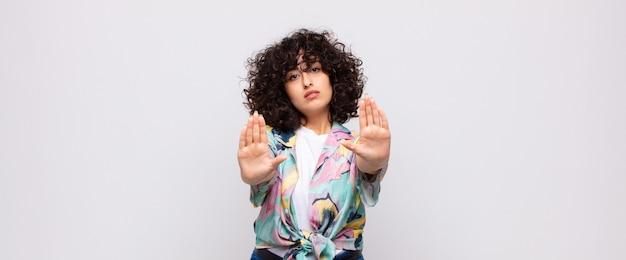 Młoda poważna ładna kobieta z kręconymi włosami