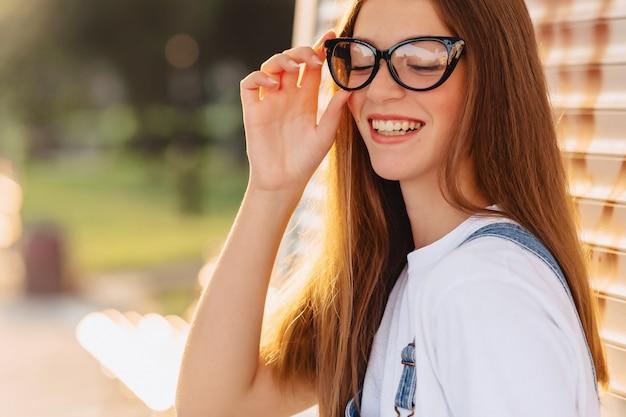 Młoda pozytywna atrakcyjna ładna dziewczyna w eleganckich szkłach przy ranku promieniami słońca