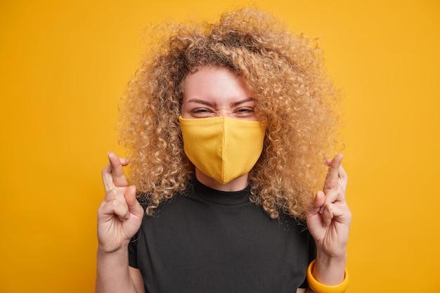 Młoda pozytywna kobieta ma jasne kręcone włosy krzyżujące palce przewiduje dobre pozytywne wyniki, ma nadzieję, że spełnią się marzenia, nosi czarną koszulkę i jednorazową maskę, aby zapobiec rozprzestrzenianiu się wirusa na żółtym tle
