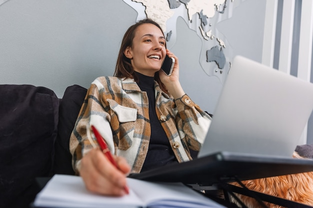 Młoda pozytywna kobieta rozmawia przez telefon podczas pracy przy laptopie