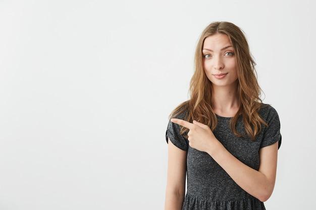 Młoda pozytywna ładna dziewczyna uśmiecha się wskazujący palec w stronie.