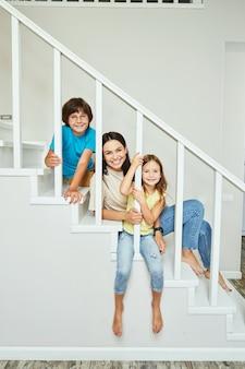 Młoda pozytywna mama z synem i córką siedzą razem na schodach w domu i uśmiechają się do siebie