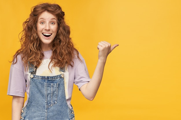 Młoda, pozytywna, ruda kobieta, nosi niebieski kombinezon i fioletową koszulkę, uśmiecha się szeroko, wskazuje kciukiem miejsce na kopię ze zdziwionym wyrazem twarzy