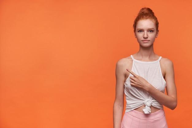 Młoda pozytywna, urocza kobieta ubrana w rude włosy w węzeł, stojąca na pomarańczowym tle w zwykłych ubraniach, uśmiechająca się lekko do kamery i pokazująca na bok palcem wskazującym