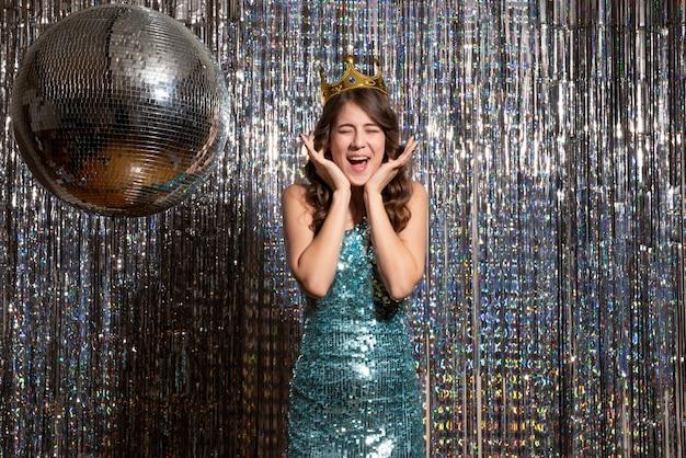 Młoda pozytywna uśmiechnięta pani ubrana w niebiesko-zieloną błyszczącą sukienkę z cekinami z koroną na imprezie