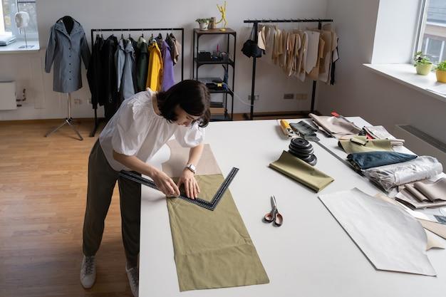 Młoda praca krawiecka z projektantem tkanin, właściciel atelier mierzy wzór rysowania tkaniny na ubrania
