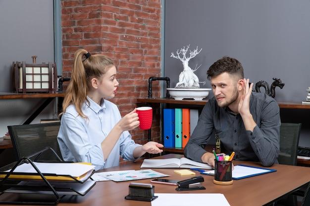 Młoda pracowita pracownica i jej męski współpracownik siedzący przy stole omawiają jedną ważną kwestię w biurze