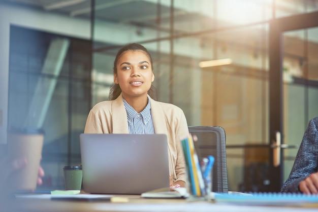 Młoda pracownica biurowa rasy mieszanej pracuje na laptopie w nowoczesnym biurze, patrząc na bok i