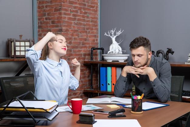 Młoda pracownica i jej męski współpracownik siedzą zmęczeni przy stole w biurze