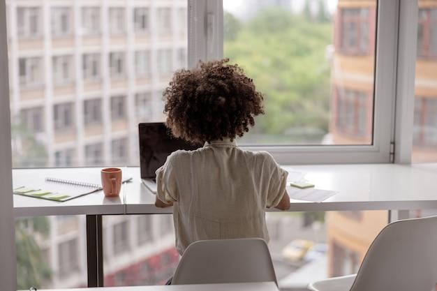 Młoda pracownica korzystająca z laptopa podczas pracy