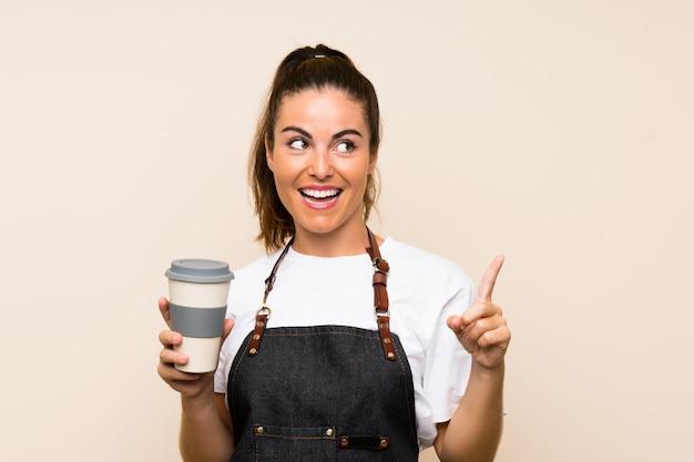 Młoda pracownik kobieta trzyma kawę na wynos, zamierzając zrealizować rozwiązanie, podnosząc palec w górę