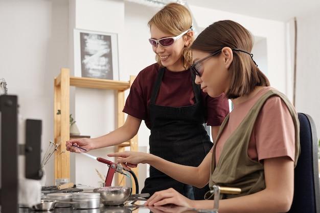 Młoda praktykantka w okularach ochronnych wskazuje na palnik, podczas gdy inna kobieta trzyma długi szklany przedmiot nad strumieniem ognia