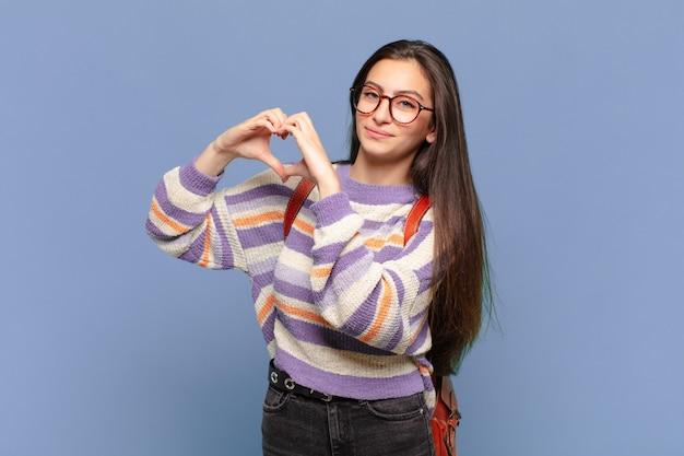 Młoda prewoman uśmiechnięta i czująca się szczęśliwa, słodka, romantyczna i zakochana, tworząca kształt serca obiema rękami. koncepcja studenta
