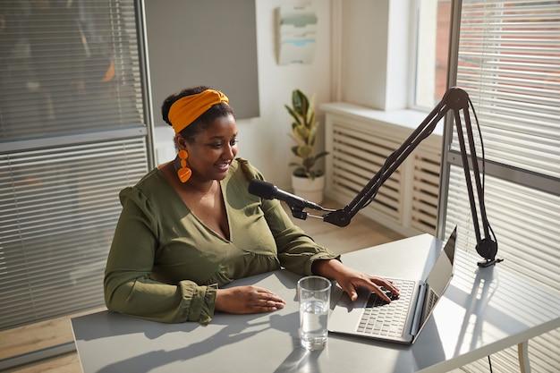 Młoda prezenterka radiowa siedzi przy stole, wpisując na komputerze przenośnym, mówiąc do mikrofonu podczas pracy w radiu