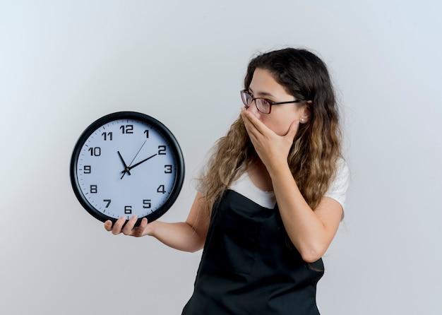 Młoda profesjonalna fryzjerka kobieta w fartuch trzymając zegar ścienny patrząc na to obejmujące usta ręką jest w szoku stojąc nad białą ścianą