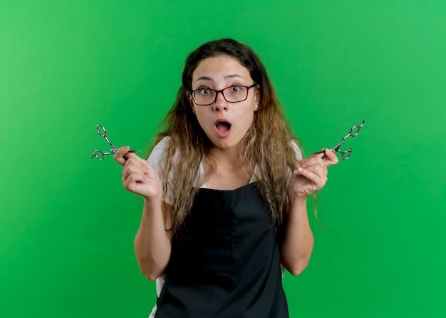Młoda profesjonalna fryzjerka kobieta w fartuchu hlolding nożyczki jest zaskoczona i zdumiona
