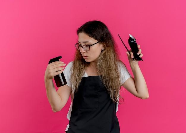 Młoda profesjonalna fryzjerka kobieta w fartuchu trzymając grzebień trymera i spray wyglądający na zdezorientowanego próbuje dokonać wyboru