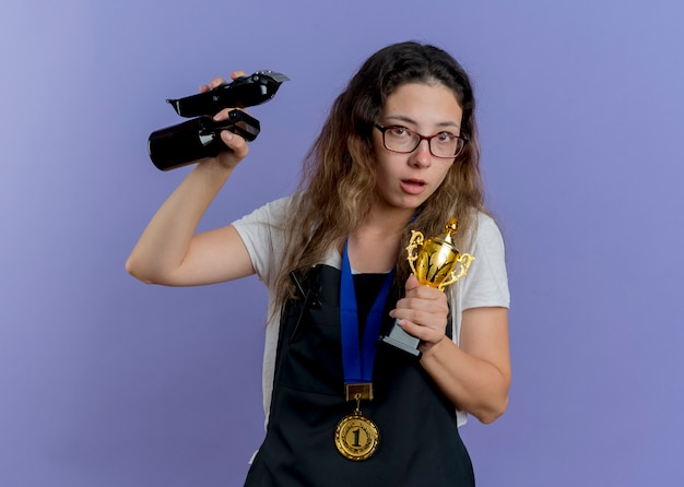 Młoda profesjonalna fryzjerka w fartuchu ze złotym medalem na szyi trzymająca trymer i trofeum patrząc z przodu zmartwiona stojąc nad niebieską ścianą