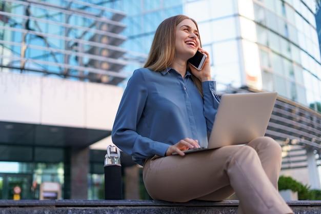 Młoda profesjonalna kobieta siedzi na schodach przed szklanym budynkiem, trzymając laptopa na kolanach i rozmawiając przez telefon komórkowy
