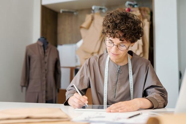 Młoda projektantka koncentruje się na przeglądaniu cyfrowych modeli nowej kolekcji mody
