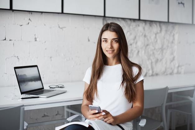 Młoda projektantka korzystająca z laptopa i telefonu komórkowego w poszukiwaniu inspiracji czytająca nowy magazyn.