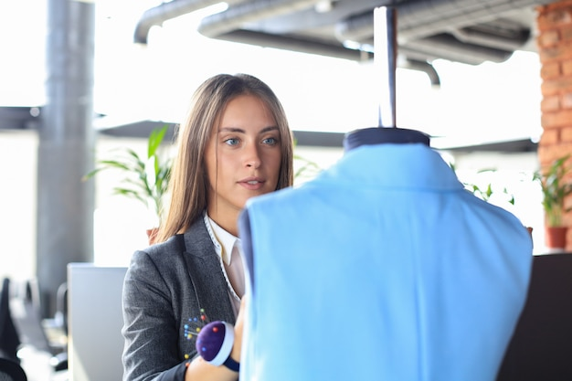 Młoda projektantka mody pracująca w swoim atelier nad nowymi ubraniami.